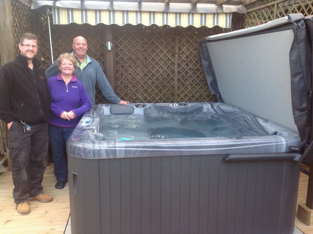 Jamie handing over a new spa to mr mrs spooner for Mr and mrs spa